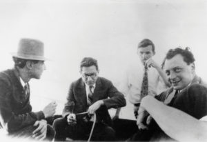 Old black and white photo of four men sitting together