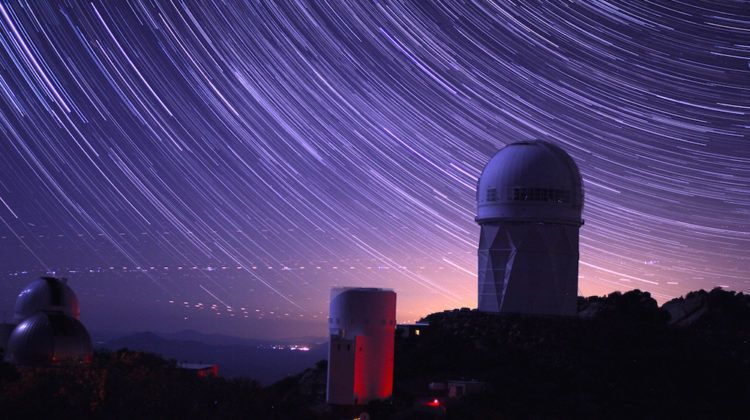 Star trails take shape around the 14-story Mayall Telescope dome in a long-exposure image
