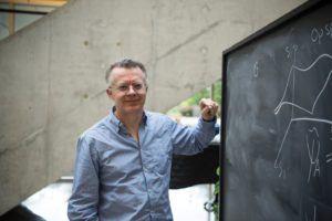 Le physicien Lucien Hardy près d'un tableau noir, craie en main