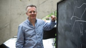 physicist Lucien Hardy leans against a blackboard, chalk in hand.