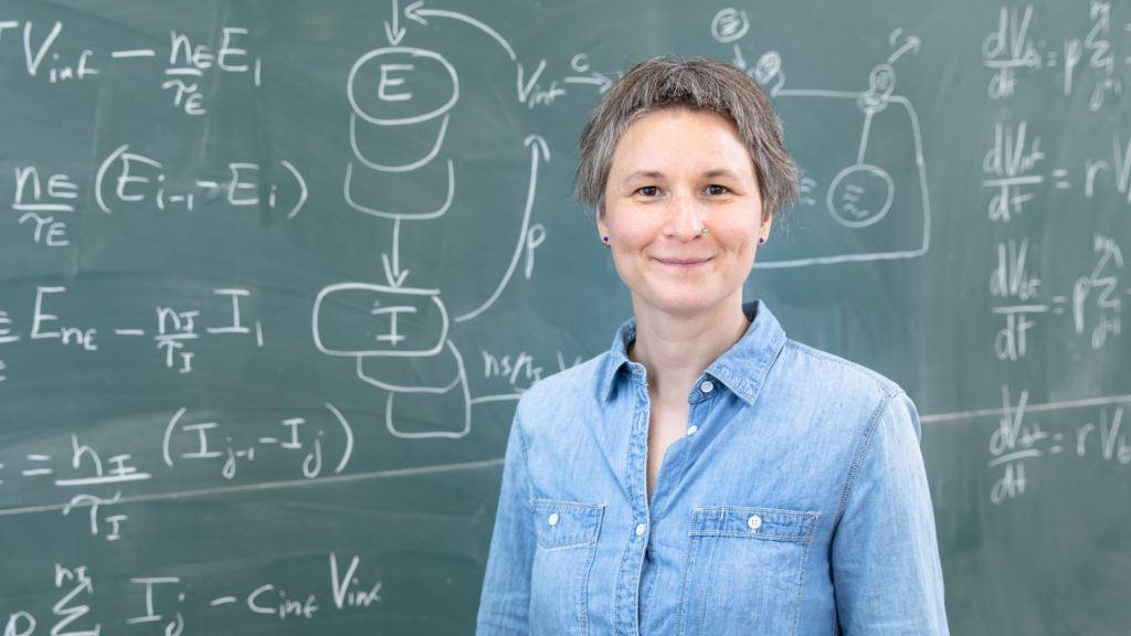 Woman in front of blackboard