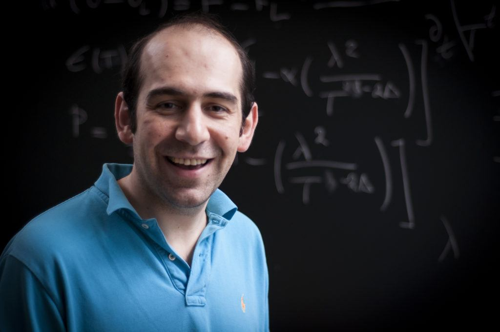 Three-quarters portrait of a man in front of a blackboard of equations
