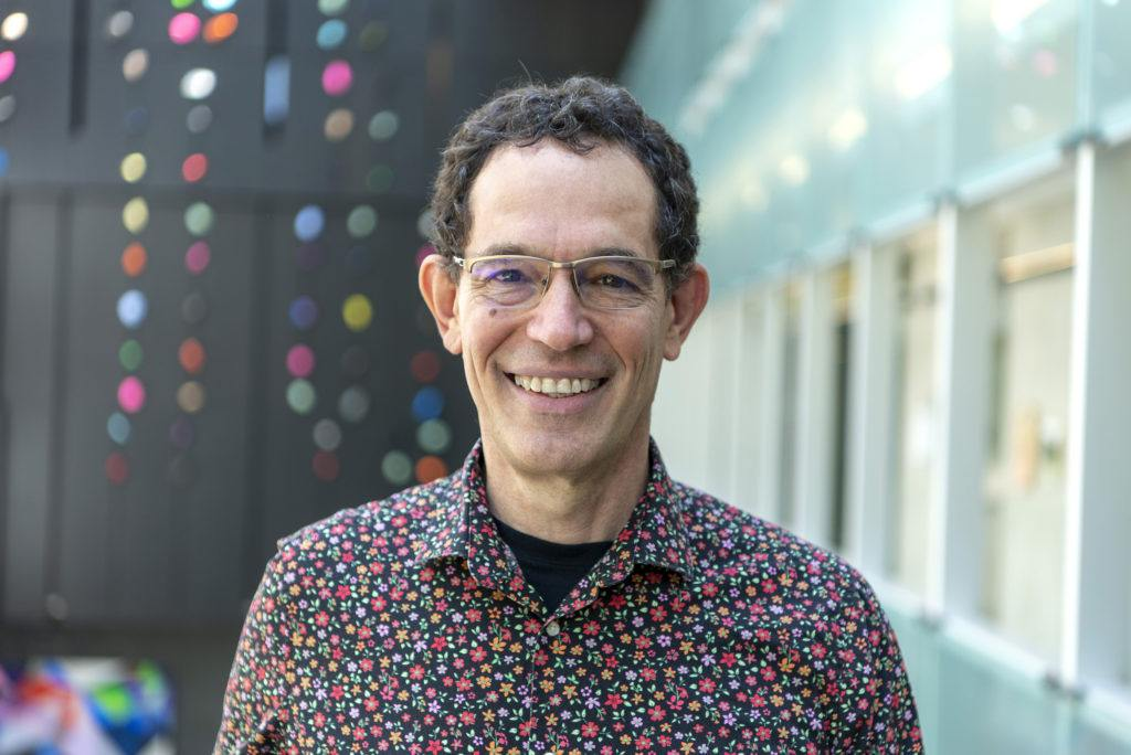Portrait of a man with a floral shirt, glasses, and a big smile