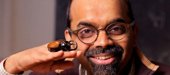 Portrait of a man with a giant beetle on the back of his hand