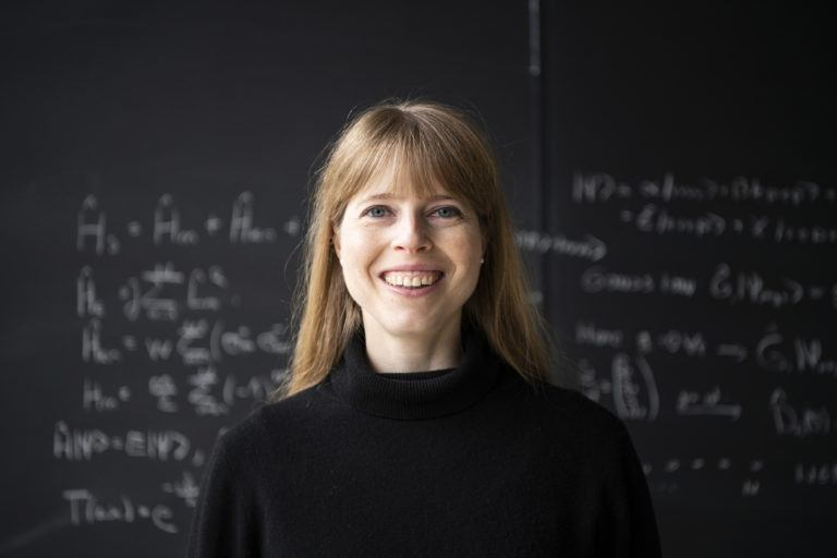 Associate Faculty member Christine Muschik. Photo of a blonde woman in a black sweater standing in front of a blackboard with equations on it.