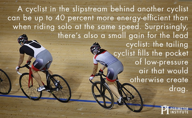 Two cyclists biking on an indoor track