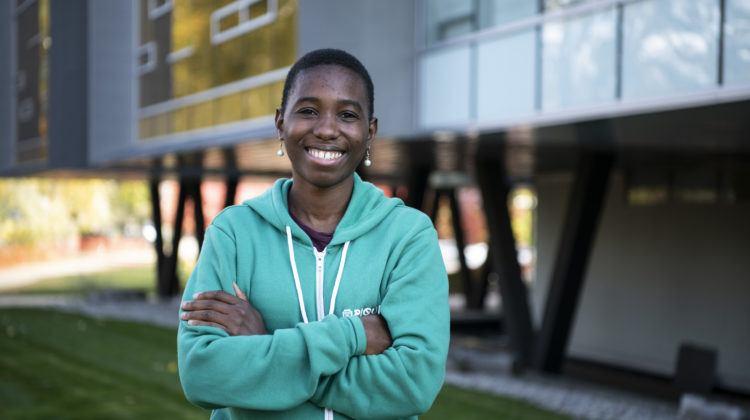 Woman in green sweatshirt in front of Perimeter Institute